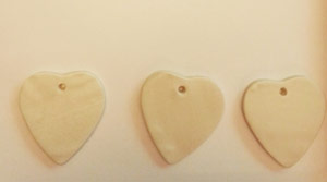 Cutting heart out of clay for Christmas ornaments