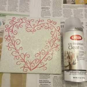 Spraying your painted ceramic tile with a clear acrylic coating